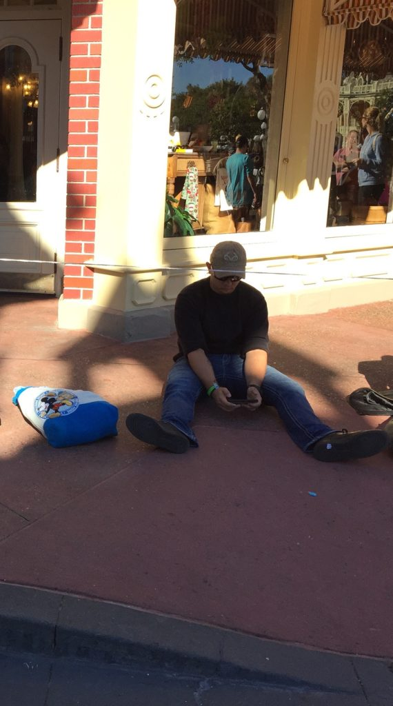 Sitting on a sidewalk waiting for the Disney parade